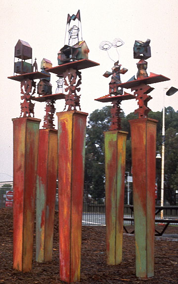 full shot of totems, towers topped with african inspired metal sculptures