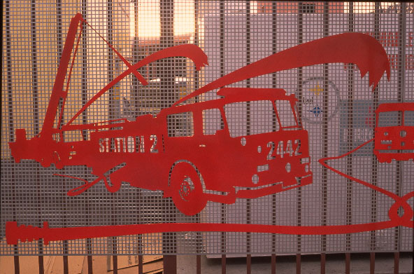 red fire engine cutout attached to a fence grating
